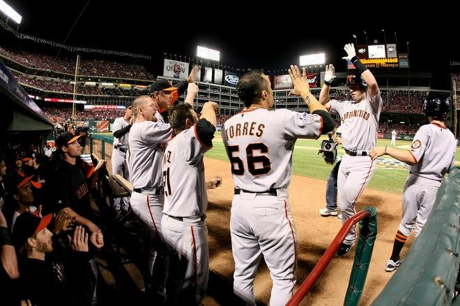 Buster Posey #28 (R) of the San Francisco Giants is congratulated by his teammates in the dugout after he scored on a solo home run in the eighth inning against the Texas Rangers in Game Four of the 2010 MLB World Series at Rangers Ballpark in Arlington on October 31, 2010 in Arlington, Texas...